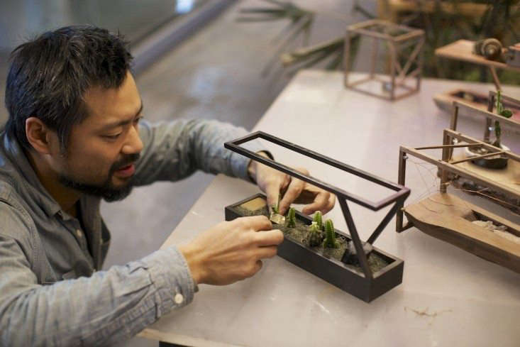 Bui carefully places plants into one of his mini terrariums. Photograph by Freunde von Freunden.
