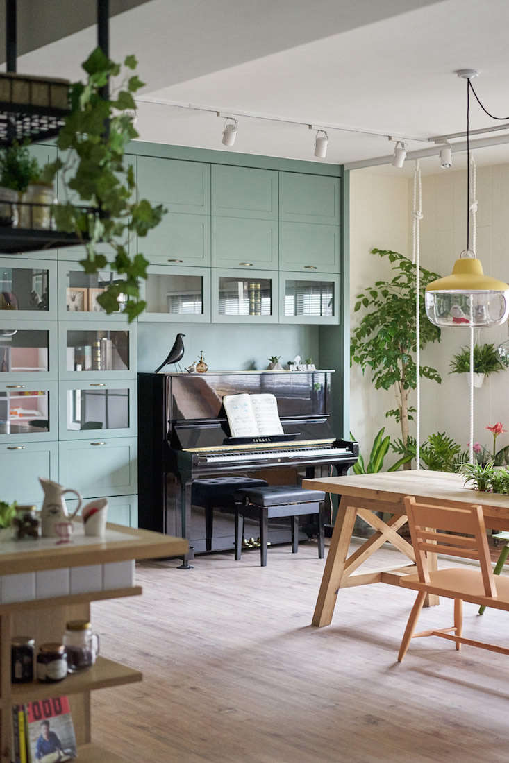 A storage and bookcase wall has a recessed nook, making the piano&#8