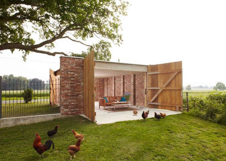 A remisenpavillion—a multi-use garage in the farmlands of Lower Saxony—designed by Bremen-based Wirth Architekten for a country house estate, serves utilitarian needs like car and tractor storage, as well as whimsical ones: as a loggia for summertime outdoor parties. Photograph by Christian Burmeister, courtesy of Wirth Architekten.