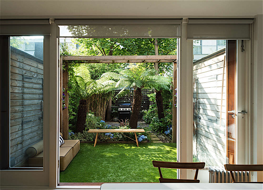We have always conceived the first part of our garden as an extension of our kitchen/dining area. In order to achieve this, we had custom sheds built, with shed walls that seem like a continuation of the indoor walls. The sheds were much more expensive than buying them off the shelf but actually very reasonable when you think that we have gained a room.