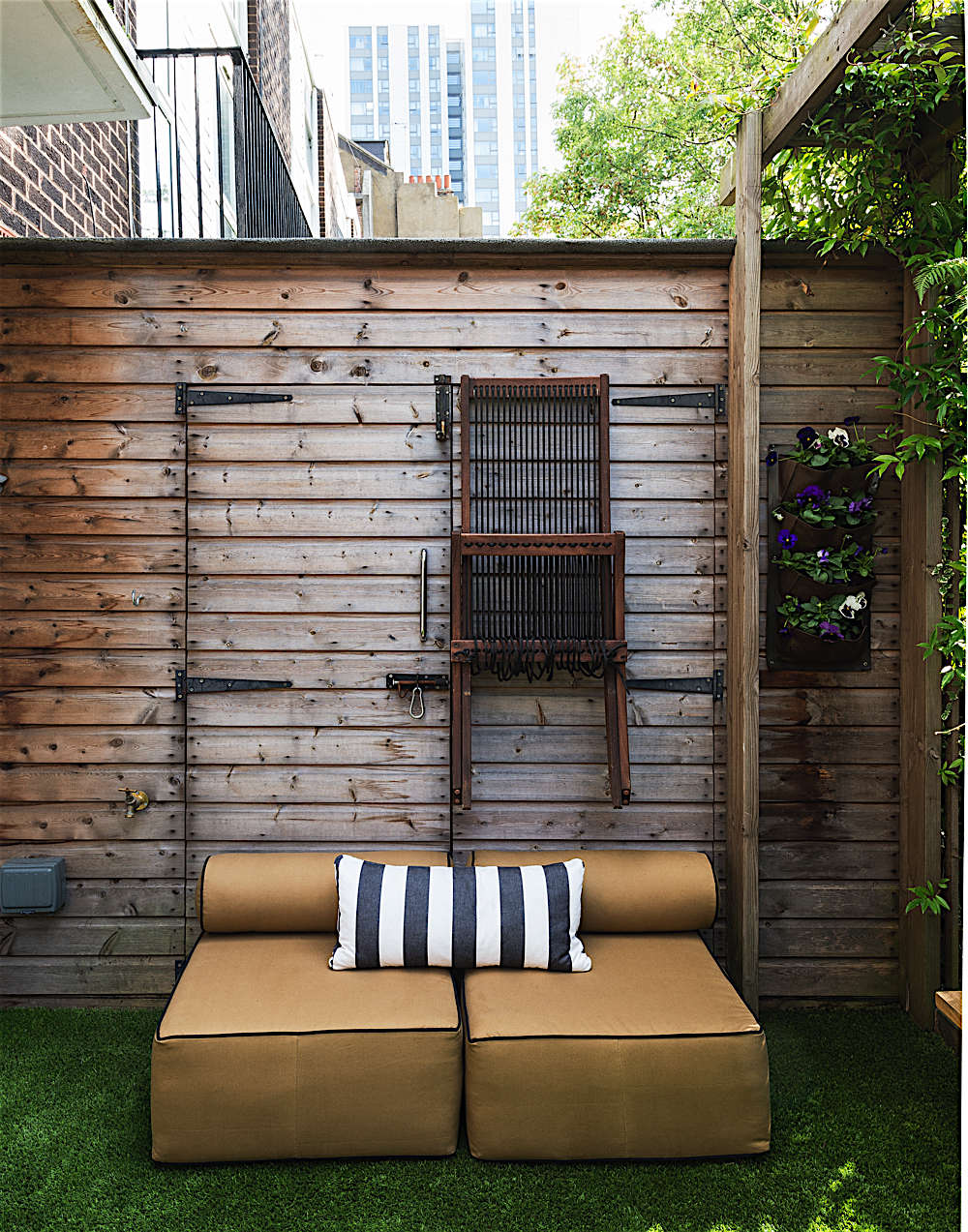 I designed simple outdoor sofas from foam blocks and had them covered with Dyed Cotton Duck with a showerproof finish from Russell & Chapple. When it rains and during the winter, the sofas move into the sheds.
