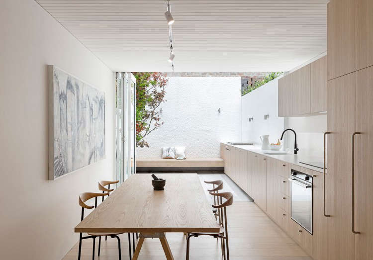 Custom cabinets of limed oak with Dekton counters run uninterruptedly from indoors to out. The floor is also limed oak that shifts to concrete tiles. The refrigeratorand pantry are concealed in full-height cabinets next to the &#8