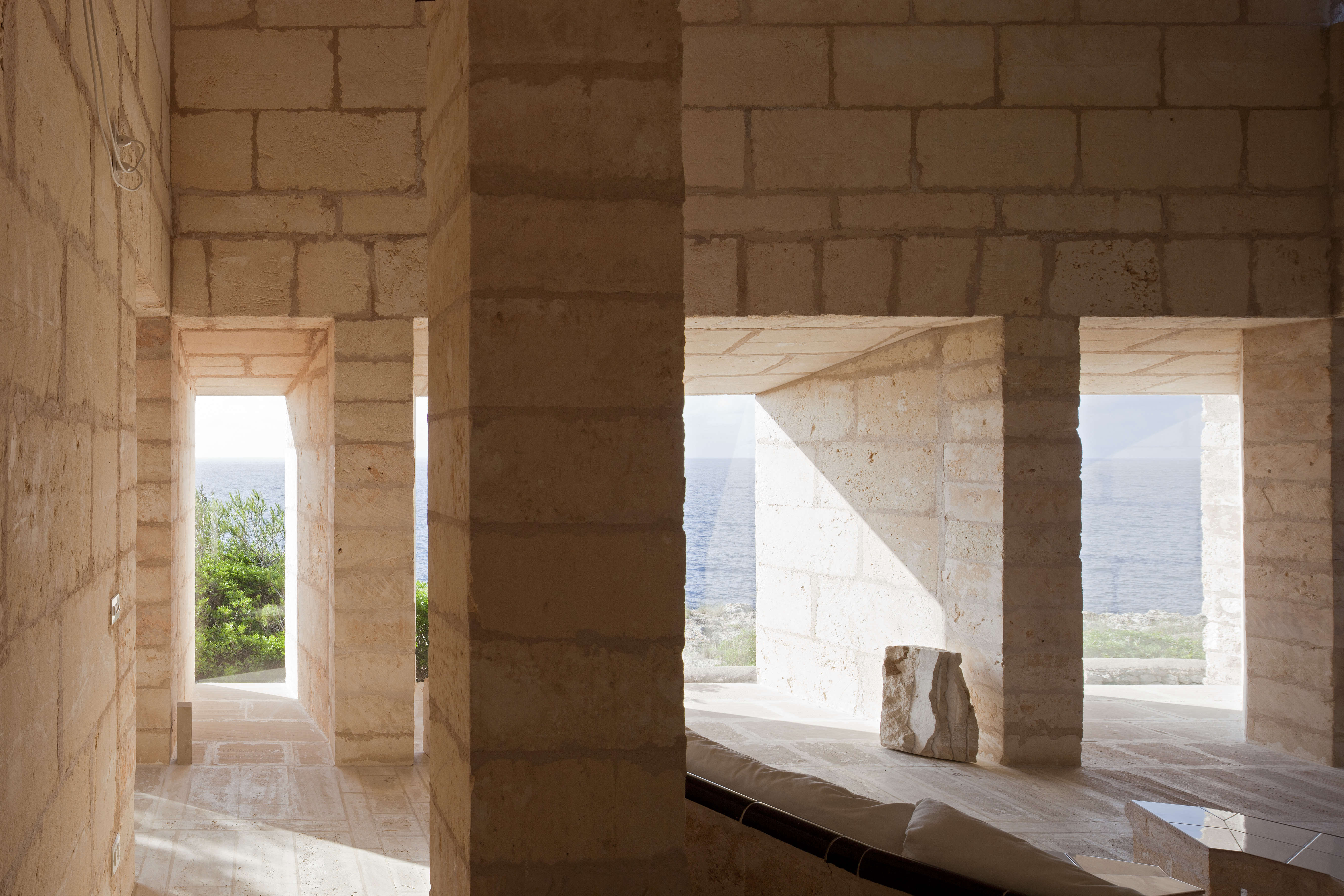 The monumental spaces create a mise-en-scène framing the sea, trees, and sky.