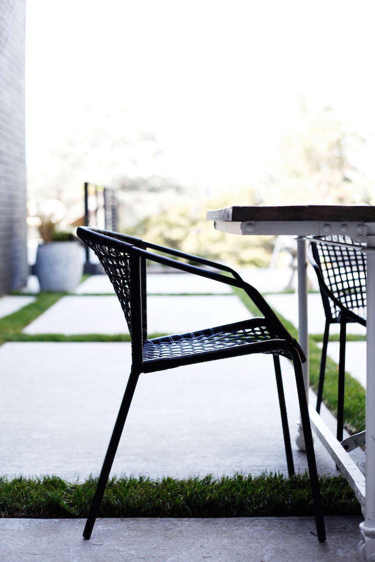 The black dining chairs are Sophia Chairs woven of weather-resistant resin rattan; $89.95 apiece from CB