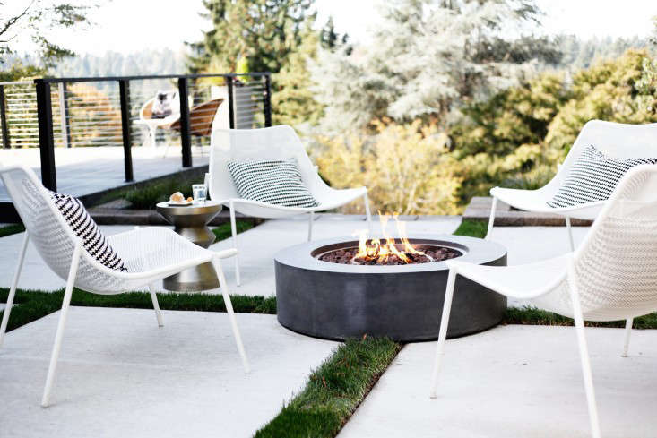 An outdoor lounge area has a fire pit as a focal point; white Soleil Lounge Chairs chairs with a durable powder coated finish are $399 apiece from Room & Board. A round Topanga Natural Gas Fire Table is $