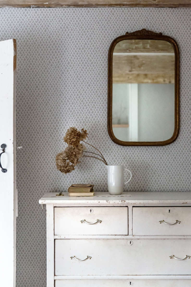 In a pitcher instead of a vase, dried hydrangeas are in motion, spilling out against a static backdrop of Farrow &Ball wallpaper. Photograph by Beth Kirby of Local Milk.