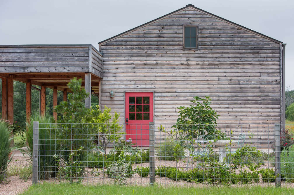 Around the corner, the detached porch building is covered in weathered cedar siding.