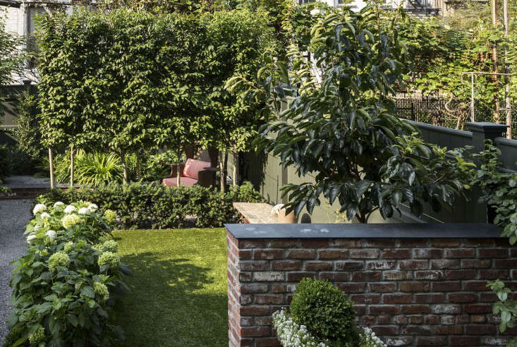 Garden designer Susan Welti of Foras Studio designed a structured hardscape—with masonry retaining walls, a bluestone terrace, a vegetable parterre, and espaliered fruit trees—to the scene for apared-down palette of a white garden designed for a five-story townhouse in Brooklyn's Carroll Gardens neighborhood. Photograph by Matthew Williams for Gardenista.