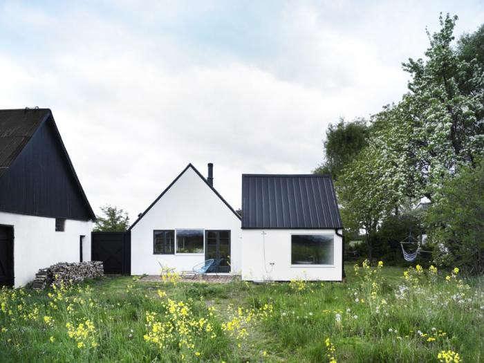 black-white-facade-wildflower-meadow-hammock-metal-roof-firewood-hoo--chairs-gardenista