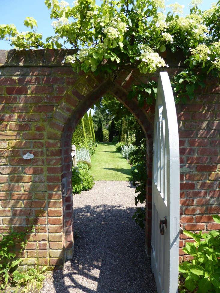 wollerton-garden-brick-wall-gate-hydrangea-petiolaris-gardenista