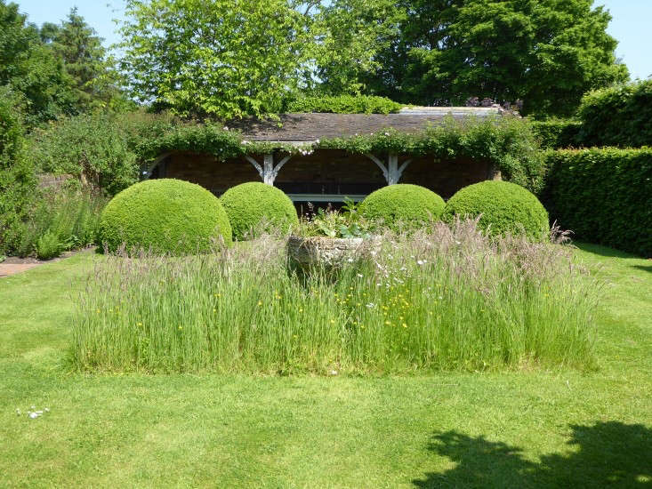 """A stone """"font"""" is surrounded with a square of unmown meadow—a simple but incredibly effective feature. Photograph by Clare Coulson, from \10 Garden Ideas to Steal from Wollerton Old Hall in Shropshire."""
