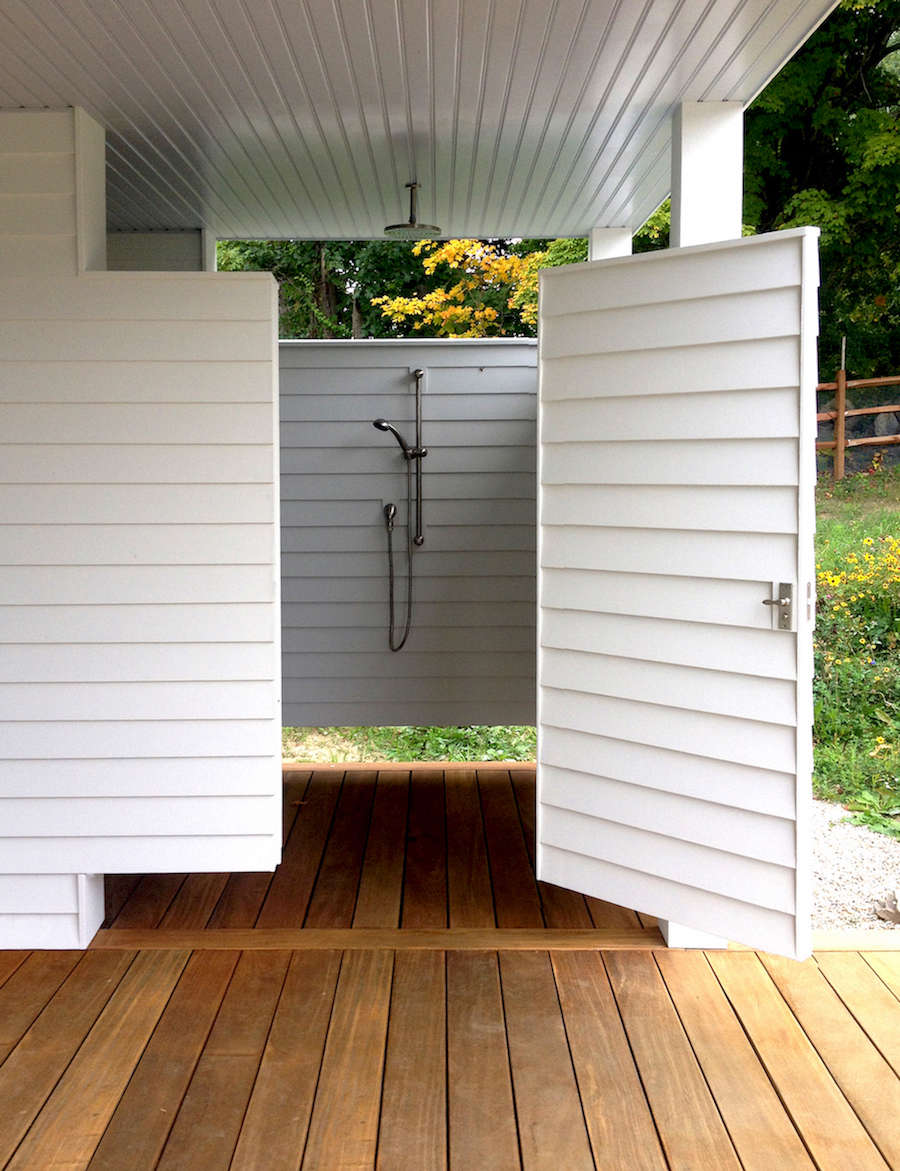 Behind the pool is an outdoor shower and changing room with a rain-style showerhead and a bench.