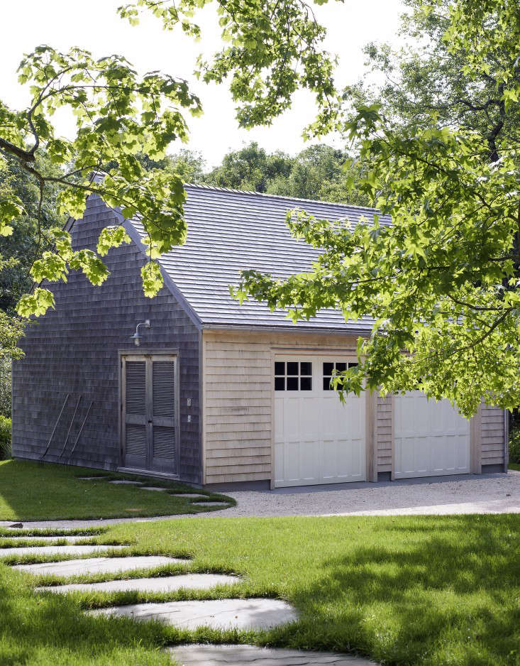 The compound of barn-like structures includes a guest barn, living barn, and master bedroom barn. A permeable gravel driveway softens the effect of the hardscape around the garage.