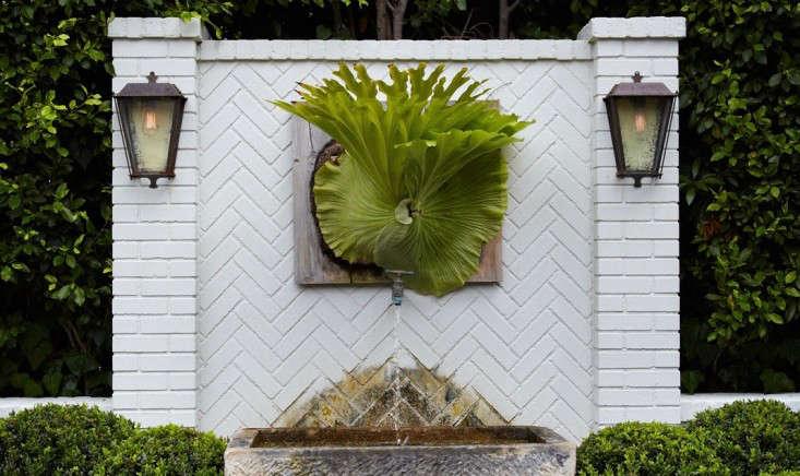 wall-lanterns-wall-fountain-shrubs-white-brick-staghorn-fern-succulents-herringbone-gardenista-1 (1)