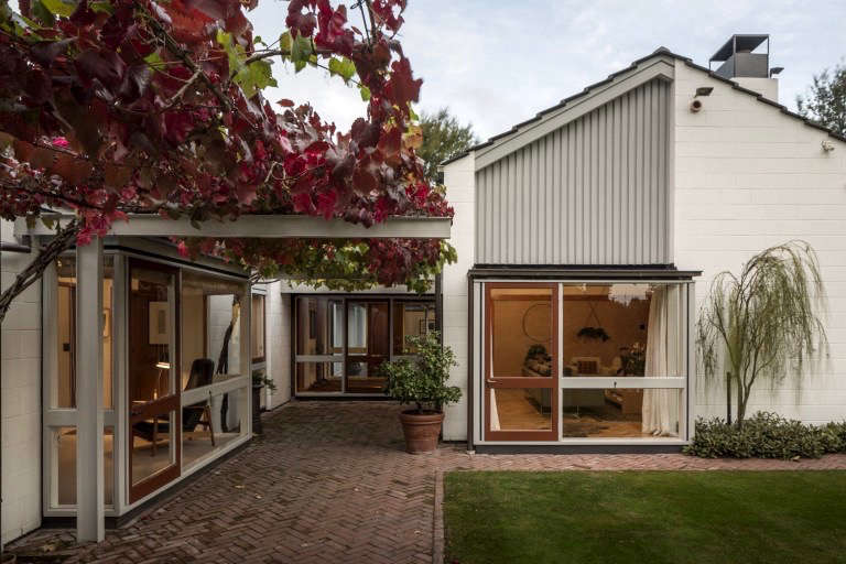 """A steel cantilevered pergola on the northwest elevation of the house creates a sheltered hallway and patio. """"The architect, Sir Miles Warren, consciously designed homes with a sense of containment and enclosure to protect the inhabitants from the cold, flat Canterbury plain where Christchurch is located,&#8"""
