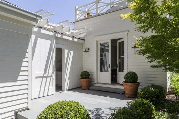 Architect Barbara Chambers flanks an entryway at her house in Mill Valley, California with identical terra cotta planters and boxwood topiaries. Photograph by David Livingston courtesy of Chambers +Chambers.