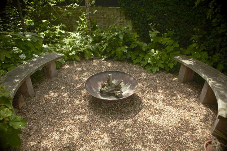 With gravel underfoot, a woodland seating circle with a fire pit is at the rear of the Andrews&#8