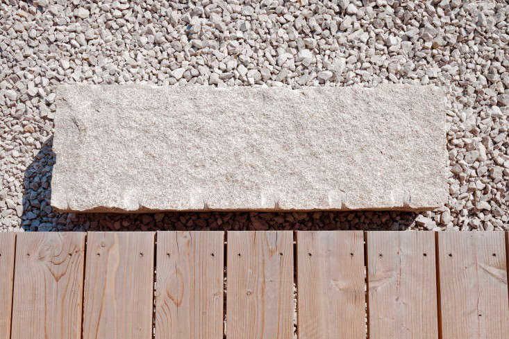 The stoop is a single stone slab set in gravel.
