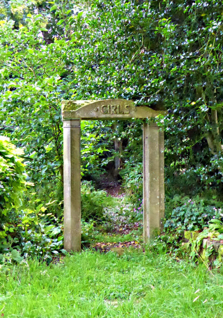 Throughout the garden arewhimsical details including asalvaged stone arch from an old school repurposed to frame the entrance into a shady walk.