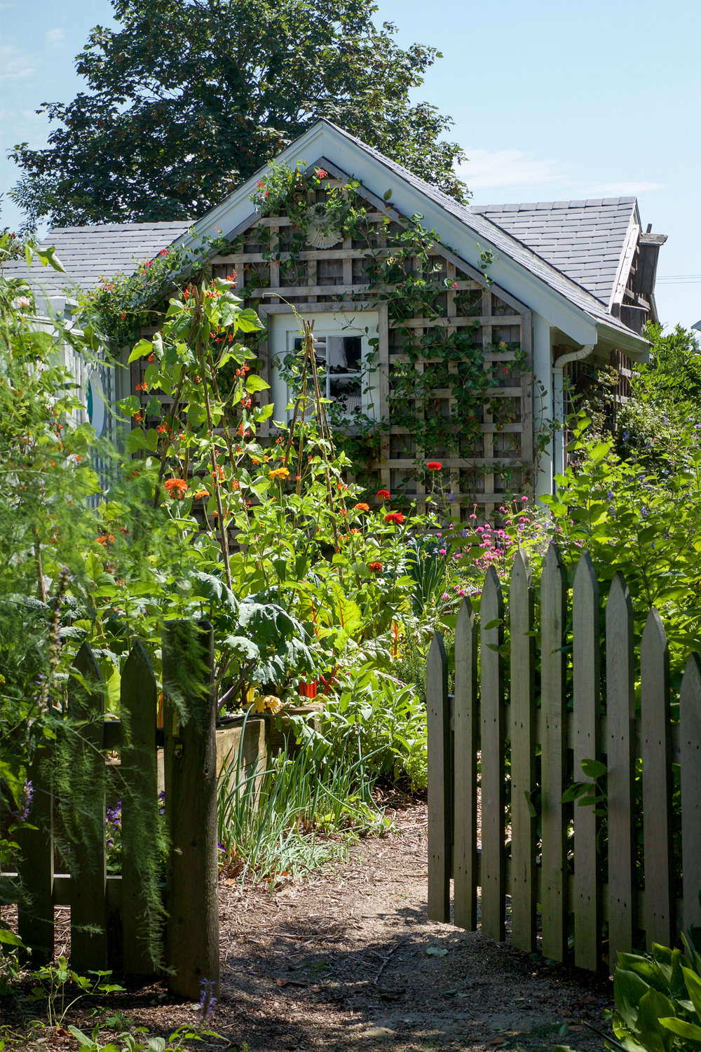 At the home of Marty Davis and Alix Ritchie, an arched gate leads to a vegetable garden patch, its shape an echo of the peaked roof of the cottage beyond.