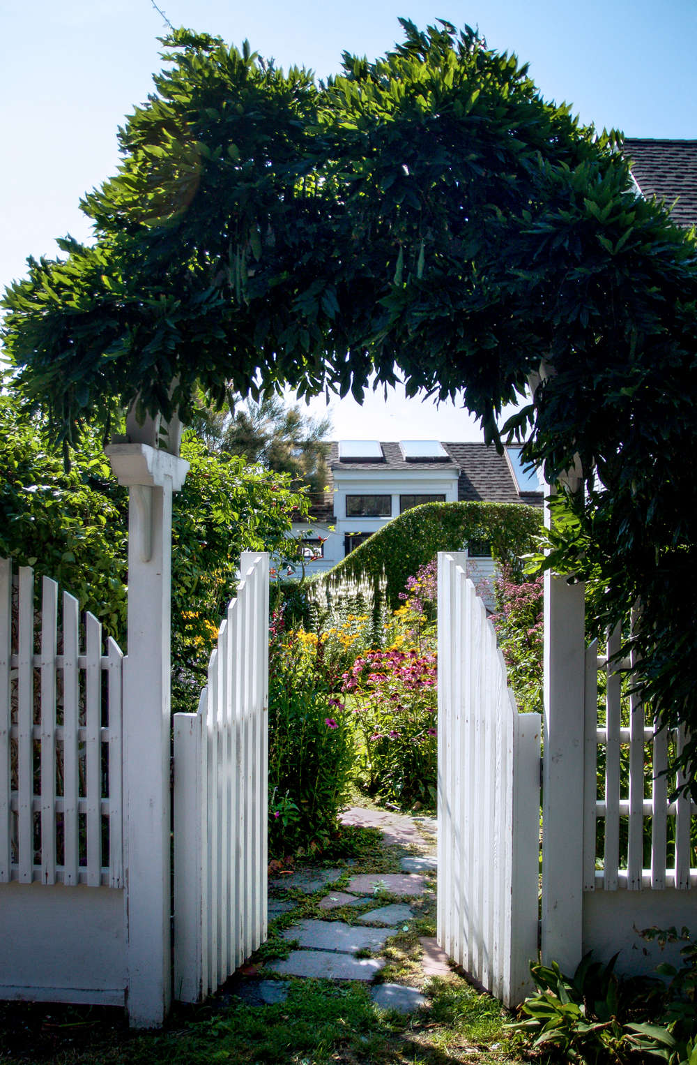 In this East End home of a local poet, a wisteria archway leading off the street is echoed in the privet hedge toward the back of the yard.
