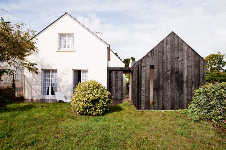For more, see Before and After: A Charred Wood Cottage, on a $45K Budget. Photograph courtesy of NeM Architectes.To create a mirror-image effect on the coast of Brittany, the architects complemented anexisting white cottage with a dark addition.