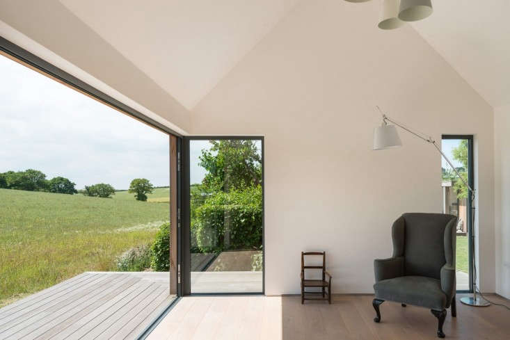 From the inside looking out, a wraparound wooden desk seems to melt into a surrounding meadow. Photograph by French & Tye courtesy of The Modern House, from A Marriage of Past and Present: A Modern English Cottage, from Another Century.