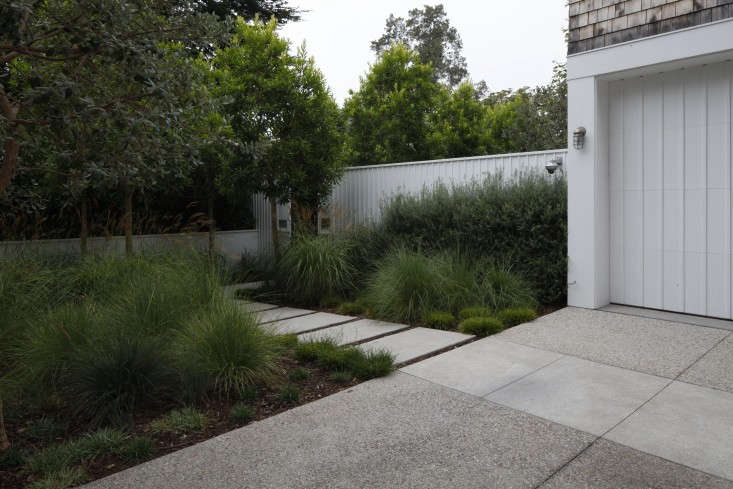 A poured concrete driveway connects visually to the pavers on a front path in the Pacific Palisades neighborhood of Los Angeles. See more of this project at Landscape Architect Visit: A Refined Family Garden with Flexible Play Zones. Photograph by Art Gray.