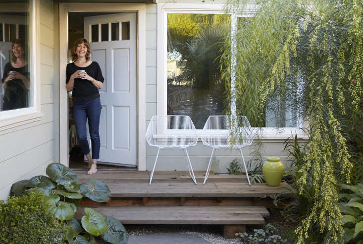 """Flora Grubb loves enclosed spaces. """"We live in the garden. We dine in the garden. We sit in the garden everyday,"""" she says. """"It's not just a tangential part of our lives."""" Her porch is flanked by an Acacia cognata tree and a Farfugium japonicum 'giganteum'. The white chairs are from Bend Goods and are available atFlora Grubb Gardens."""