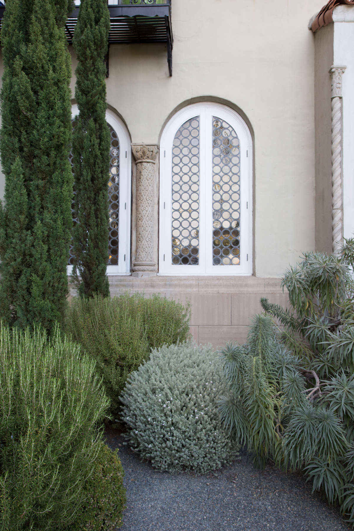 Mediterranean garden corner with leaded glass window in Santa Monica