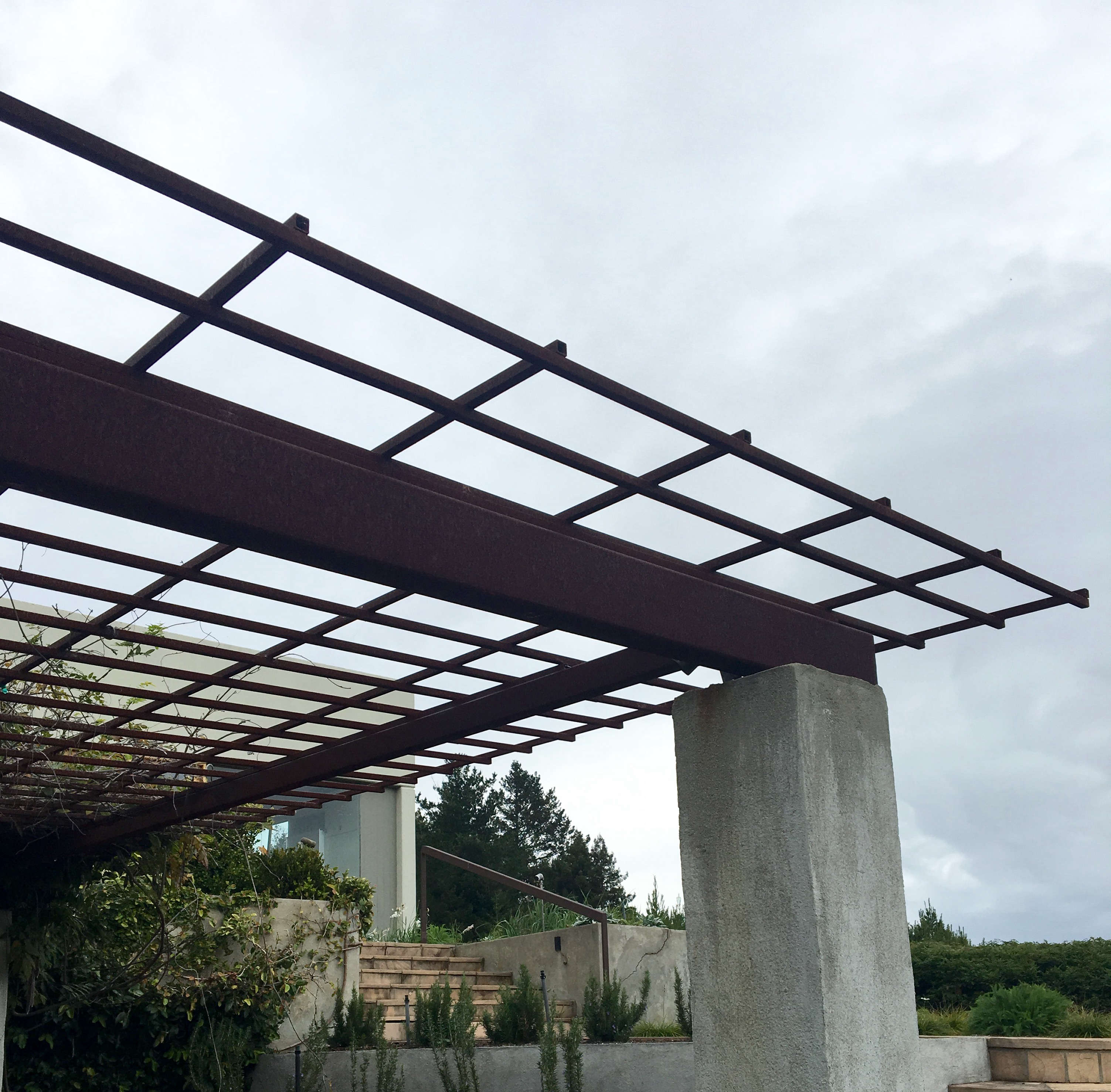 A reclaimed steel pergola with poured in place concrete columns sits atop this Mount Tamalpais property. The exposed site and the dramatic weather patterns have weathered the metal nicely and created a nice contrast to the concrete. Photograph by Kier Holmes.