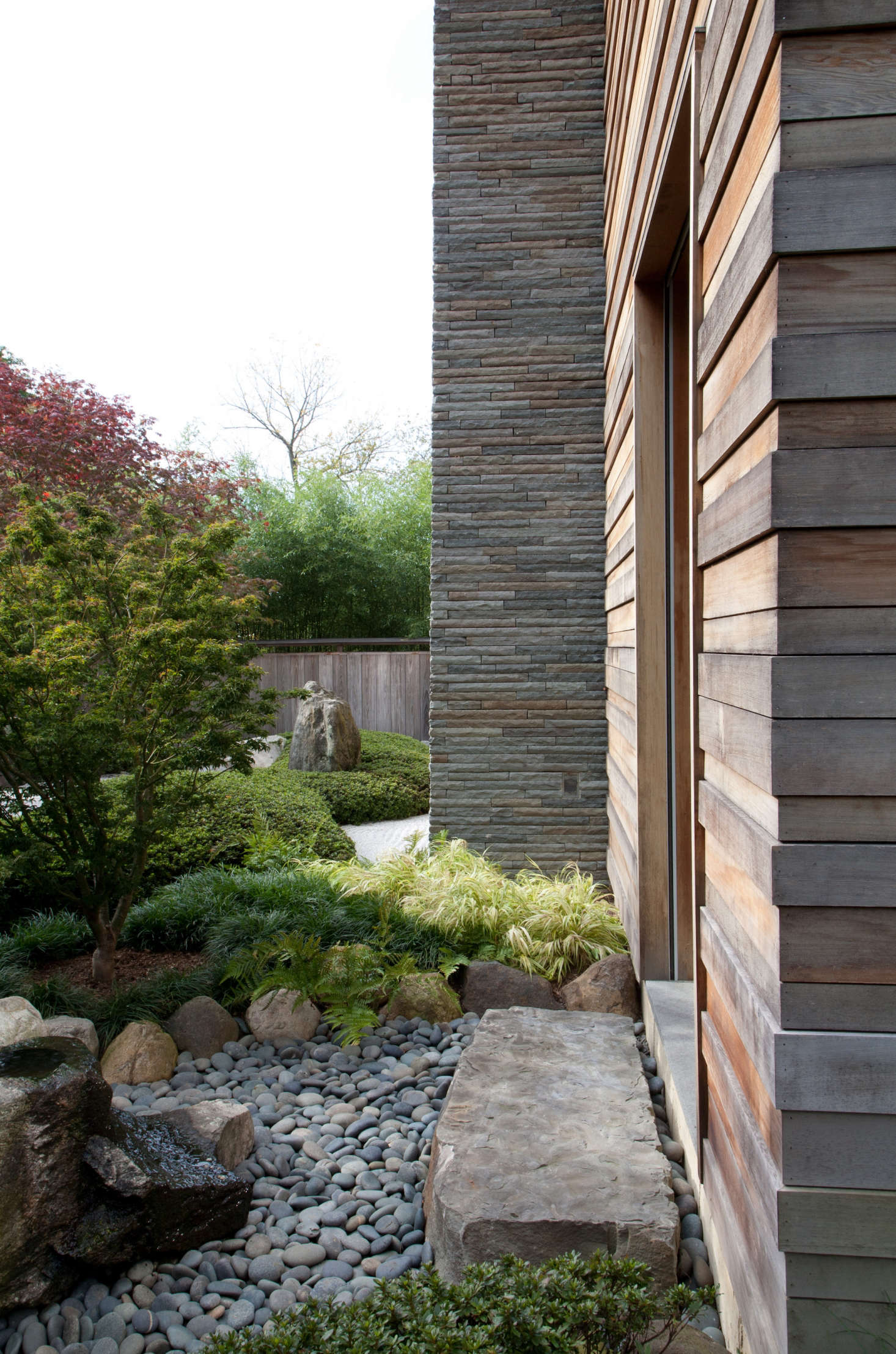 A Japanese-inspired garden features a smooth river rocks at the edge of a stone slab stoop in a Westchester County, NY landscape by designer Marc Peter Keane. Photograph by and courtesy of Don Freeman. For more, see Designer Visit: A Garden Inspired by Japan.