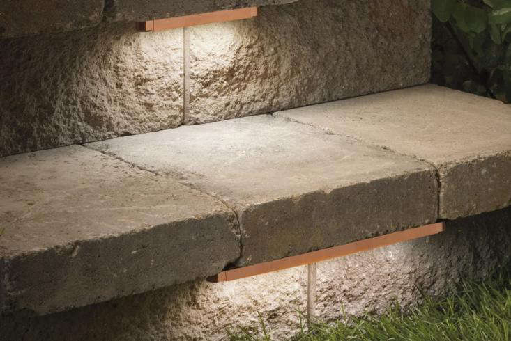 Hardscape lighting that mounts beneath the overhang on a stair tread is discreet and effectively directs light downward. For more, see Design Sleuth: Hidden Hardscape Lighting. Flexible light tape also can be used. Photograph courtesy viaKichler.