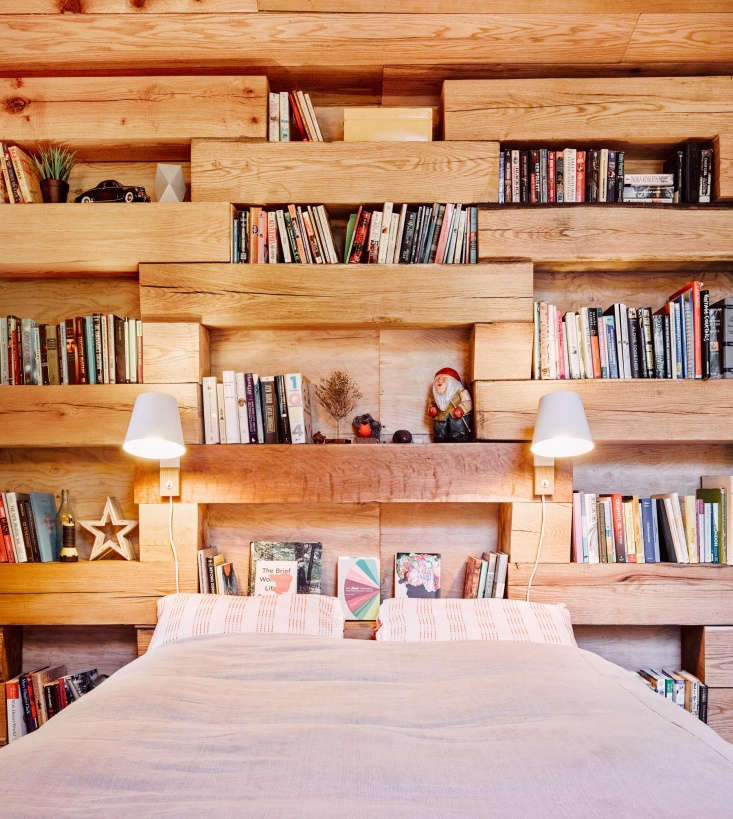 The cabin is just big enough to fit a bed, desk, and chair. Twin sconces save space and provide ample reading light; built-in shelvingholds books and serves as nightstands.