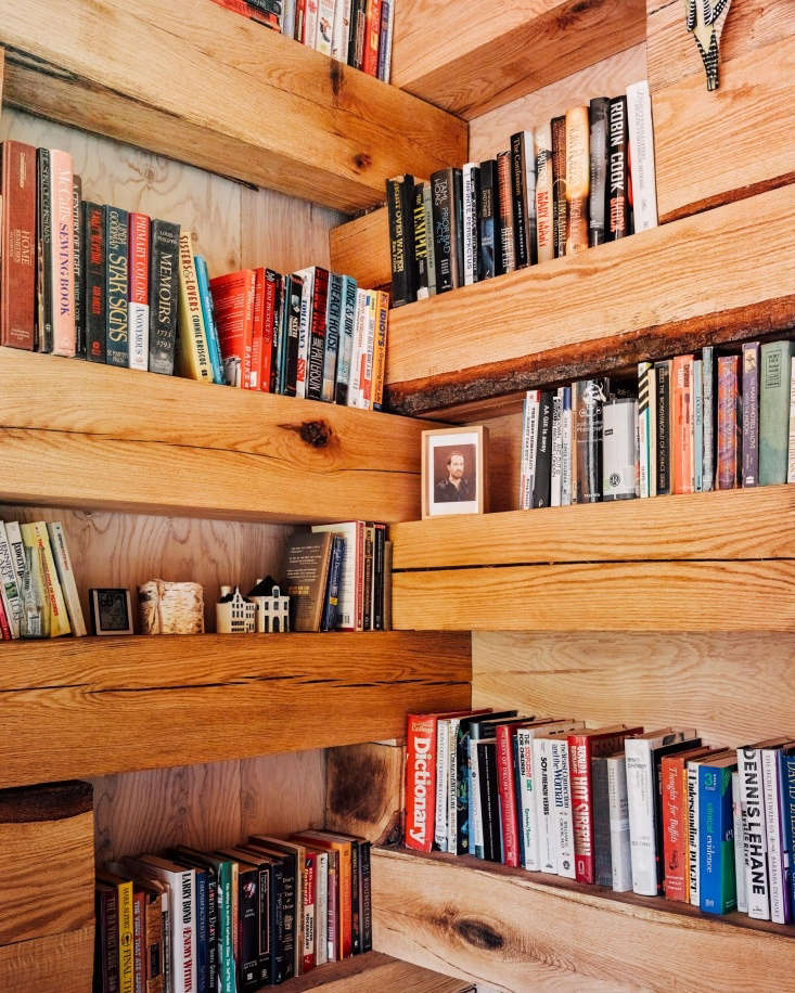Rustic built-in timber shelves line every interior wall and evoke traditional log cabins. Koxvold estimates that they hold several thousand books.