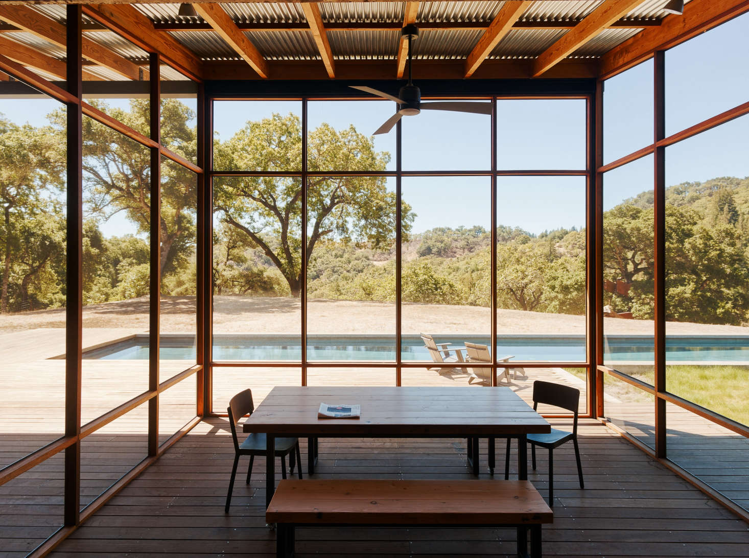 A screened dining porch by architect Malcolm Davis overlooks the pool. Both the decking and screen frame are made of rot-resistant ipe wood, while the building's framing lumber is Douglas fir. Photograph courtesy of Malcolm Davis, from Swimming Pool of the Week: A Rustic Family Campground—with a Lap Pool.