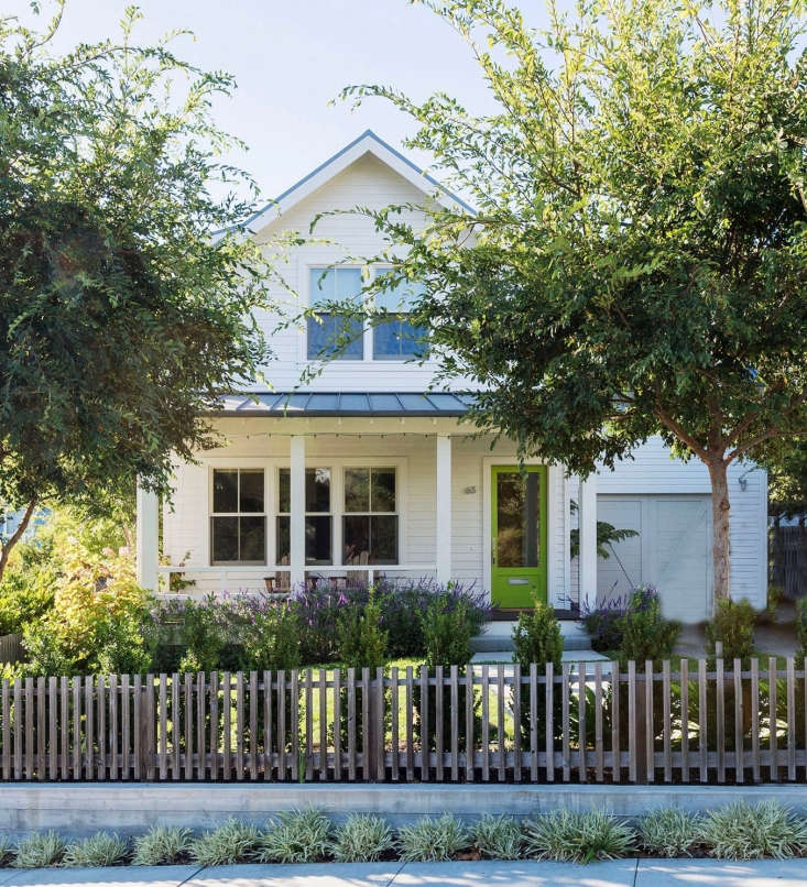 A picket fence built of \2-by-\2-inch pieces of clear cedar and a standing-seam metalroof are a nod to classic farmhouse style.