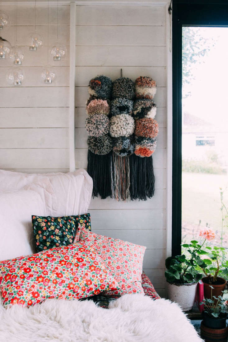 Jeska layered the daybed with colorful mix-and-match textiles, including pillows covered in floral Tana Lawn cotton fabric and a recycled wool throw. The interior paint is Bedec Eco Paint in white.