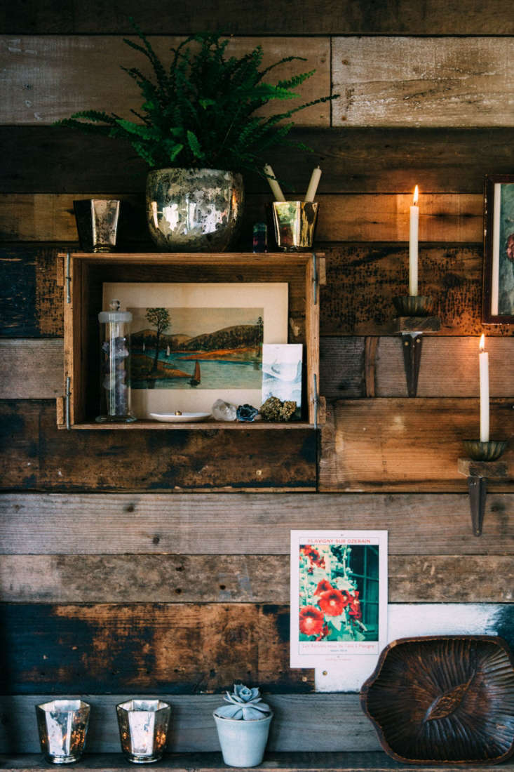 Jeska transformed found and vintage boxes into shelving that blends into the wall. A carved Swedish plate (an Etsy find) is perched on one shelf. Jeska collects the metal wall-mounted candle holders from local antique shops.
