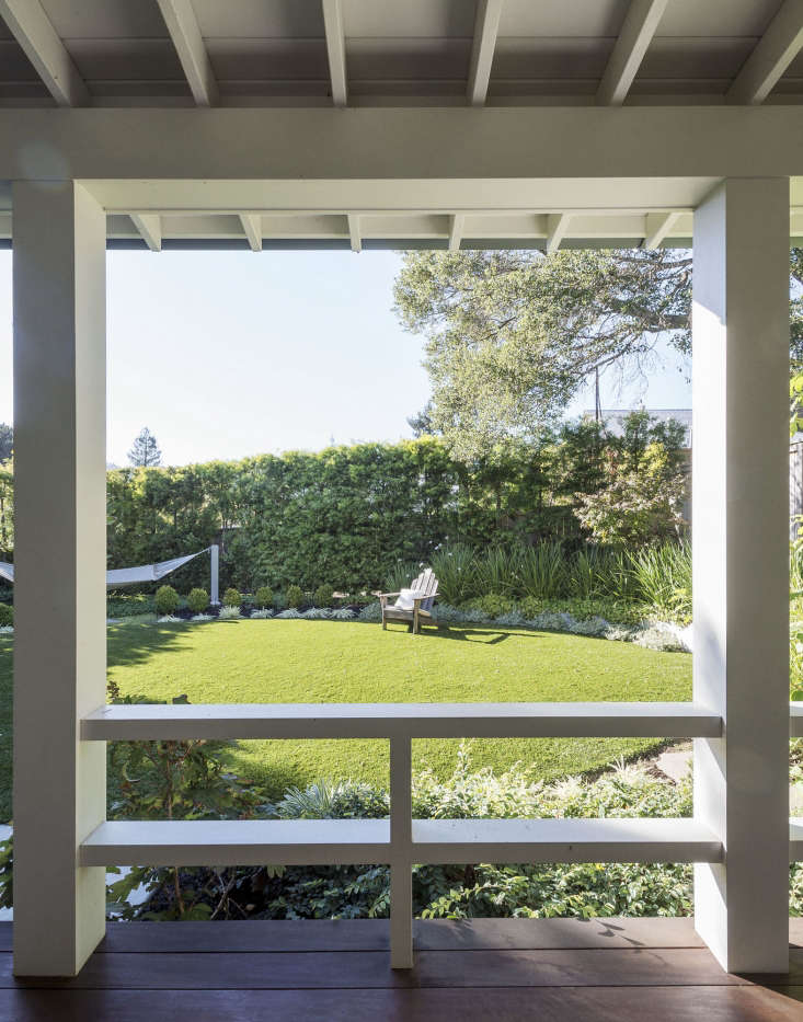 A covered porch provides shade and looks out onto aback garden with an emeraldgreen lawn. To save water in drought-plaguedCalifornia, Haegglund installed artificial turf.