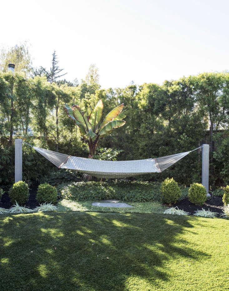 In the far corner of the garden is a hammock.