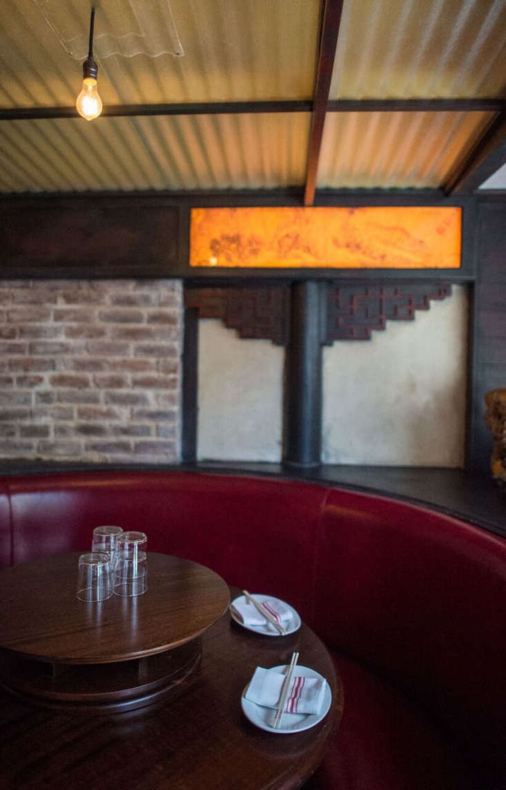 Red banquettes encircle a Lazy Susan, a nod totypical Chinese restaurants.