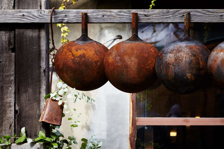 The antique, tarnished vibe extends into the garden. Shown here: retiredfrom the kitchen find a new home in the courtyard. Photograph by Levi Miller, courtesy of Kings County Imperial.