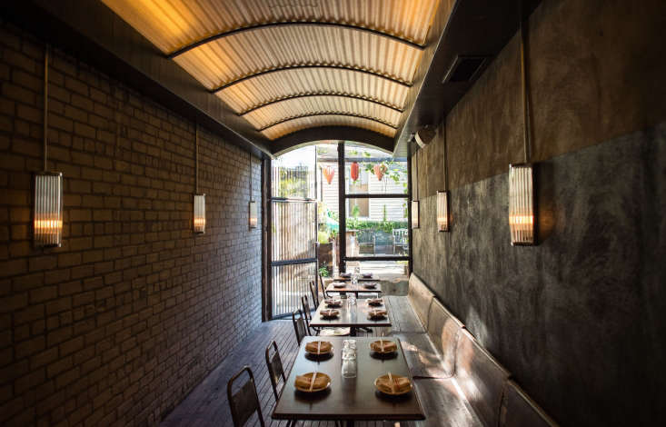 A tunnel-like dining area with wooden benches leads to the backyard garden.
