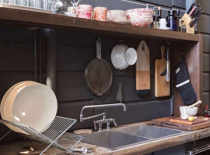 Wooden cutting boards and kitchen accessories hang on hooks against the shop&#8