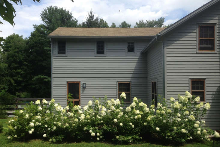 """For curb appeal, Sosa and Coe painted this farmhouse in """"serene gray"""" (Benjamin Moore's Platinum Gray), a nice backdrop for the row of white hydrangeas. Photograph by Mylene Pionilla, from Before & After: An &#8\2\16;Ugly Duckling&#8\2\17; Landscape Transformed, in NY&#8\2\17;s Hudson Valley."""