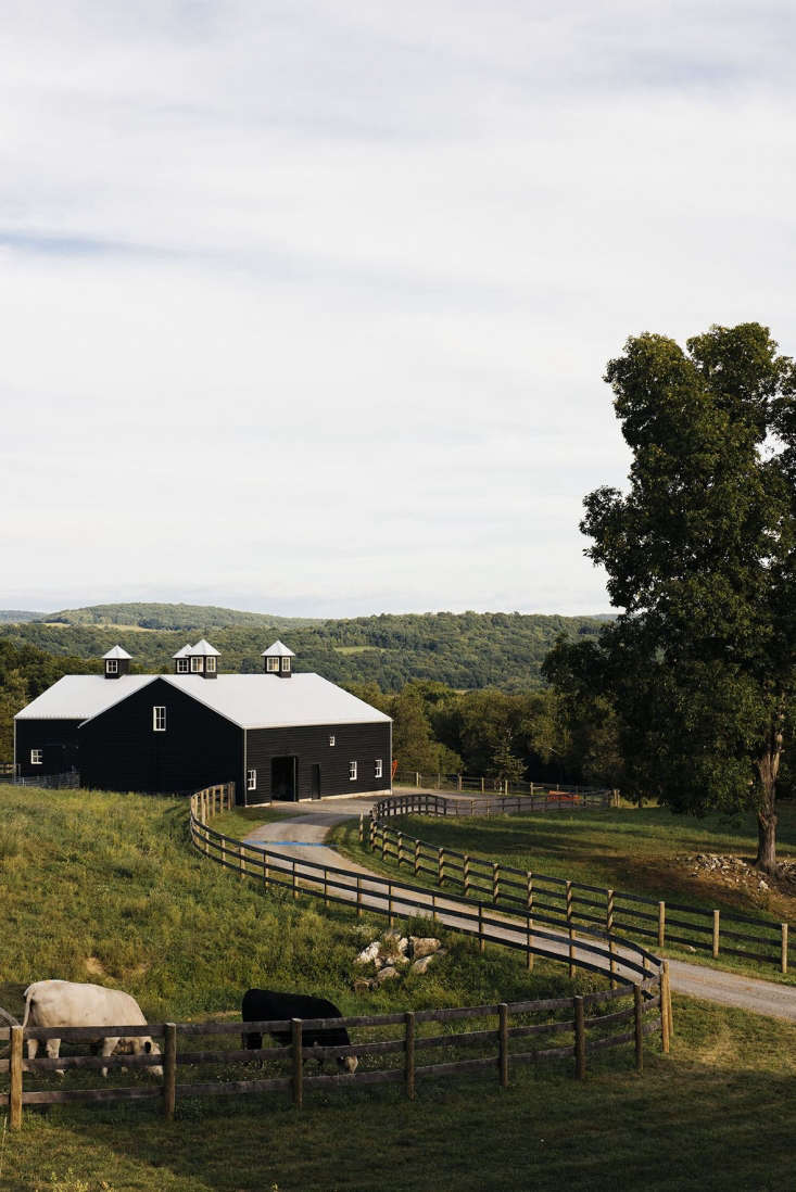 In Pine Plains, New York, the L-shaped barn at Sky High Farm has two attached volumes serving as a livestock barn and a harvest processing facility. The structure has a corrugated metal roof with wood siding painted in Benjamin Moore&#8\2\17;s Black.