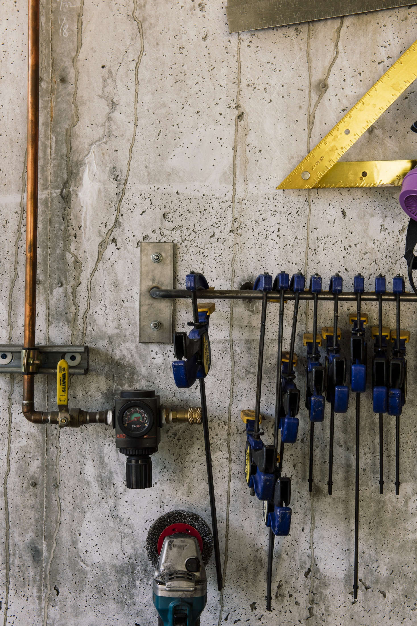 Steel hooks and bars keep shop tools like clamps and rulers in place. Exposed copper tubing is beautiful and necessary:It carries pressurized air for cleaning shop surfaces and materials.