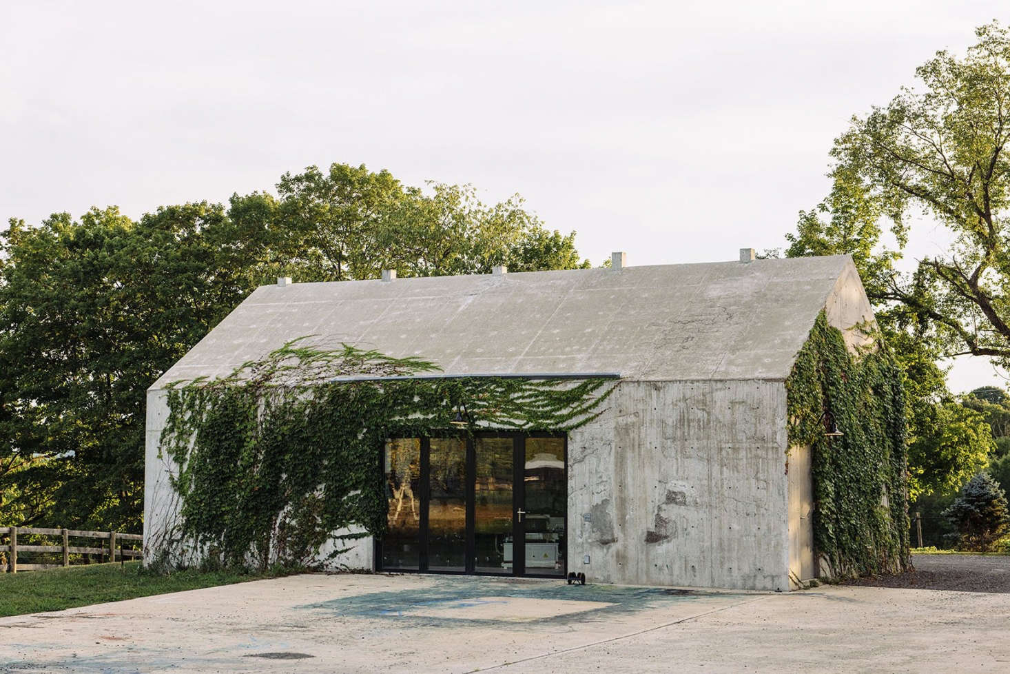 The welding studio is made of reinforced concrete, which first was poured to make three sides of the rectangular base (one side is glass), then poured inside a barn-roof-shaped form in one go.