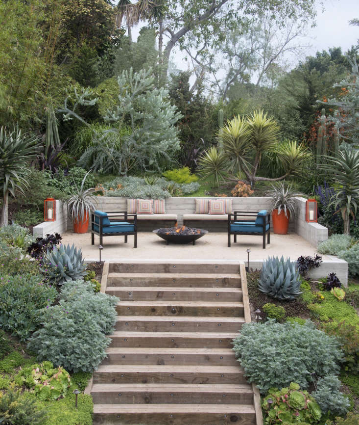 Built-in seating doubles as a retaining wall to create a sheltered spot for a fire pit in a Los Angeles garden.
